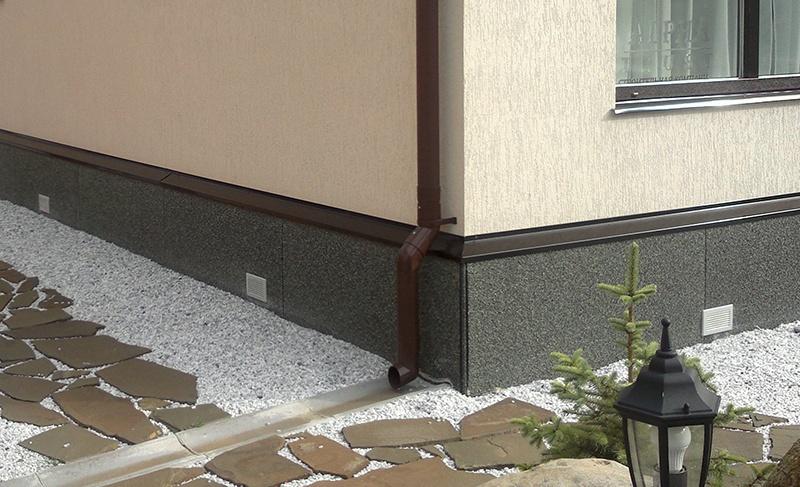 Облицовка цоколя дома пластиковыми панелями под камень
