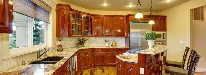 Large luxury kitchen with marble counters, and bar seating.